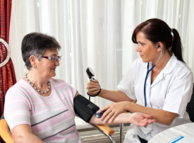 nurse checking the blood pressure of the elder woman