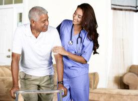 nurse assisting the elder man walking