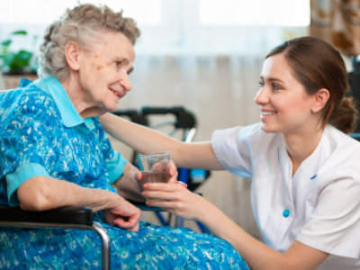 nurse giving a glass of water to the senior woman