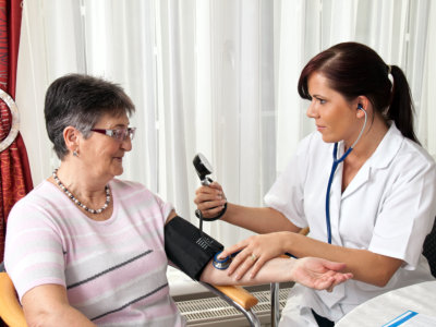 nurse checking the blood pressure of an elderly woman