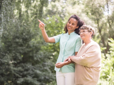 elder women and nurse strolling in the park