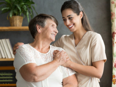 caregiver holding the hands of senior woman while smiling